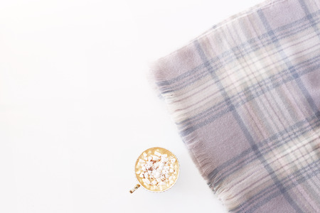 A cup of cocoa and marshmallows on a warm powdered scarf on a white background. Winter days concept. Top view, flat lay