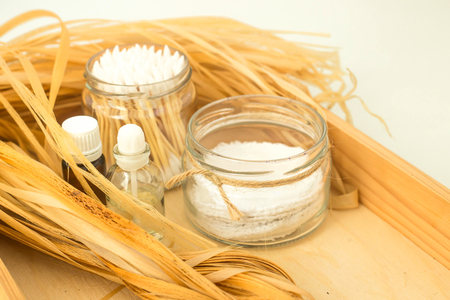Eco accessories for body care and spa - bast, loofah, wooden cotton swabs in a glass jar, essential and aroma oil on a wooden tray. Zero waste concept