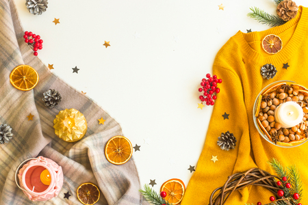Winter sweater, scarves and decorations on a white background with oranges, stars and candles. Top view, flat lay, copy space Stockfoto