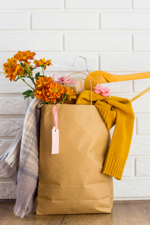 Crafting package with women's purchases on a black Friday, filled with clothes, cosmetics, flowers. Near the white brick wall. Discounts black friday concept Stockfoto