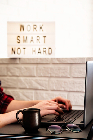 Home workplace of a freelancer at a black stylish table near the sofa and brick wall in a modern apartment. Female hands press the keys of a laptop. Work smart, no hard - written on a lamp