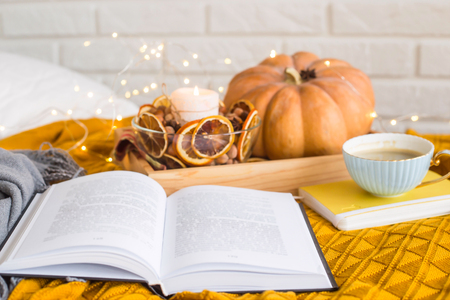 Homely cozy rest on an autumn day off - reading among blankets with a cup of coffee next to candles, dried oranges and pumpkin Banco de Imagens