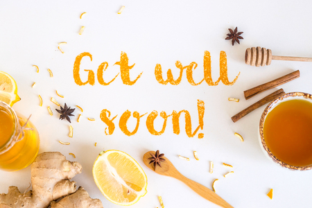 Get well soon - written from ground turmeric on a white background among the products for the treatment of common cold - lemon, honey, ginger