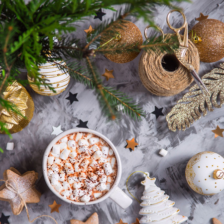 A large cup of cocoa with marshmallow sprinkled with cocoa powder stands on a gray table among Christmas decorations, fir branches, ginger cookies and shiny stars. Top view
