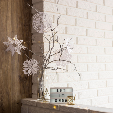Let it snow it is written on a decorative lamp next to a home winter decor with a vase with tree branches with paper snowflakes against a brick wall of an apartment