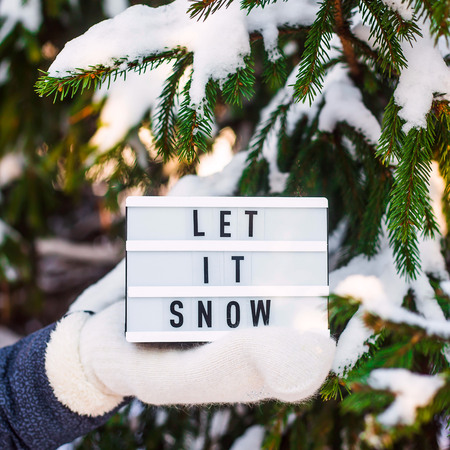 Let it snow it is written on a decorative lamp in the hand of a woman in a white mitten against the background of green spruce branches covered with snow