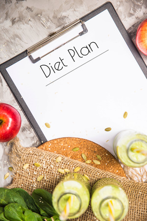 The diet plan is written on a white sheet on the tablet among the bottles of green smoothies, spinach and apples on a gray table with burlap. Weight loss concept. Top view
