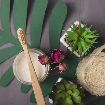 Ecological accessories for personal care and bathroom - bamboo toothbrush, washcloths, paste on green paper leaves. Zero waste concept