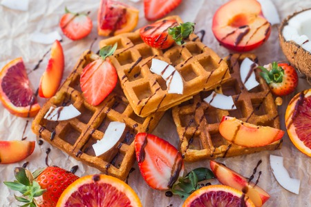 Waffles with strawberries, coconut, plum and orange with chocolate