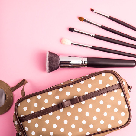 Brown polka-dot beautician with makeup brushes on a bright pink background. Retro style. Top view, flat lay