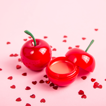 Glitter rumble in a cherry-shaped jar on a bright pink background among red shiny hearts Reklamní fotografie