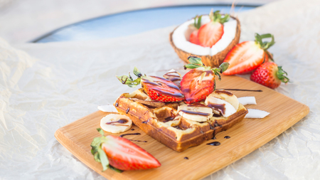 Belgian waffle with fruit and chocolate sauce is beautifully served on a wooden board. Next to strawberries and coconut Reklamní fotografie