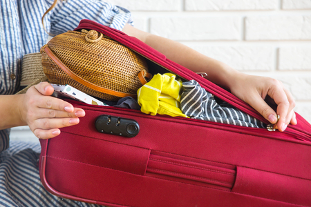 Suitcase full of womens clothing for summer holidays Imagens