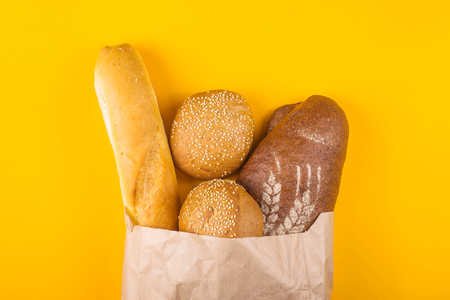 Fresh, varied bread in a paper bag on a yellow background - white baguette, dark loaf and cereal buns with sesame. Top view, flat lay