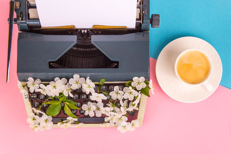 Typewriter with white flowers from the keys - spring writing creativity on the concept. On a bright pink background. Top view, flat lay Stockfoto