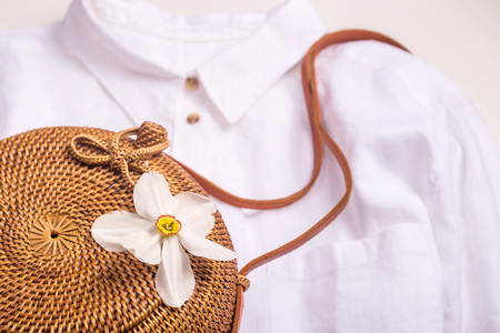 White basic shirt with stylish accessories and a wicker bag with a white flower. Top view, flat lay