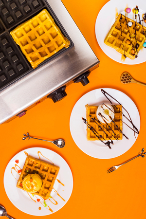 Waffle iron and ready made belgian waffles on plates on a bright yellow background. Top view, flat lay