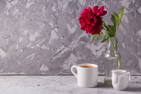 White cup of coffee next to creamer and a vase bottle with a red peony on a gray background Copy space Stok Fotoğraf
