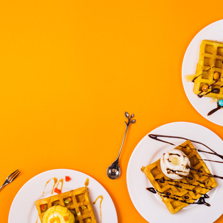 Fresh golden square Belgian waffles on plates with ice cream and toppings on a bright yellow background. Top view, flat lay. Copy space