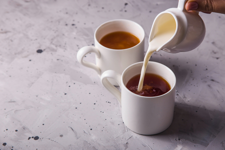 Milk pours into a cup from white creamer tea on a gray textural background