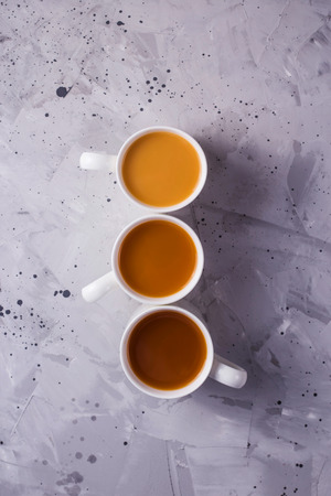 Three cups of masala tea or coffee with milk of different colors on a gray textural background. Top view, flat lay