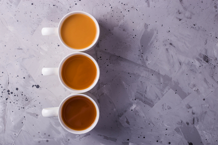 Three cups of masala tea or coffee with milk of different colors on a gray textural background. Top view, flat lay. Copy space