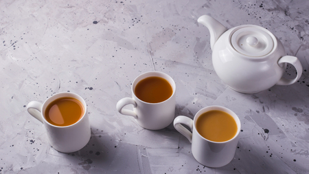 A white teapot next to three cups of tea masala or coffee with milk on a gray textural background. Top view, flat lay, copy space