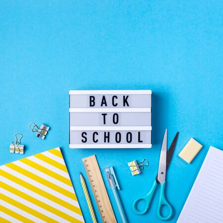 Bright modern minimalist stationery for school on a blue background next to a decorative lamp with the inscription back to school