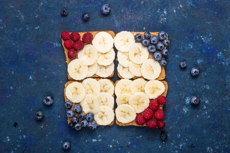Healthy sandwich breakfast with peanut butter, banana and berries on a dark blue table. Top view, flat lay Imagens
