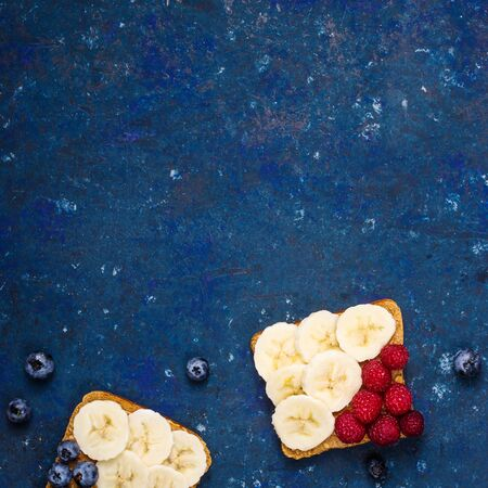 Healthy sandwich breakfast with peanut butter, banana and berries on a dark blue table. Top view, flat lay, copy space
