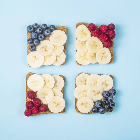 Healthy breakfast of sandwiches with peanut butter, banana and berries on a bright blue background. top view, flat lay Imagens