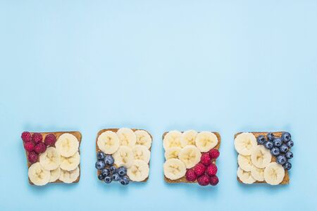 Healthy breakfast of sandwiches with peanut butter, banana and berries on a bright blue background. top view, flat lay, copy space