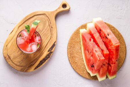 A glass of cold watermelon juice with ice and lime garnished with mint next to a few sliced pieces of watermelon. Top view, flat lay 写真素材