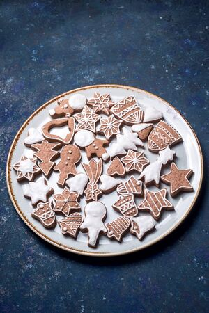 Homemade gingerbread cookie decorated with white icing on a large plate on a dark blue table. Top view, flat lay