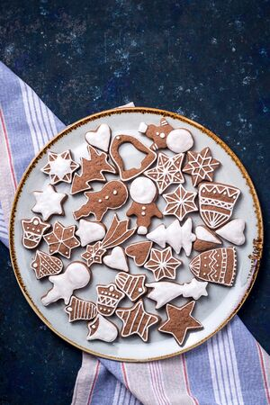Homemade gingerbread cookie decorated with white icing on a large plate with a kitchen napkin on a dark blue table. Top view, flat lay Imagens