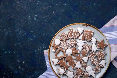 Homemade gingerbread cookie decorated with white icing on a large plate with a kitchen napkin on a dark blue table. Top view, flat lay, copy space