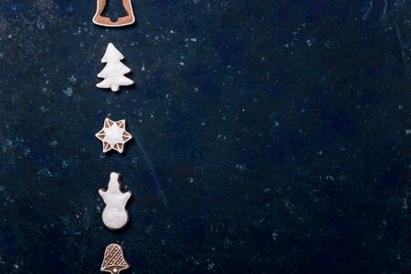 Homemade gingerbread cookie decorated with white icing on a dark blue background. Top view, flat lay, copy space