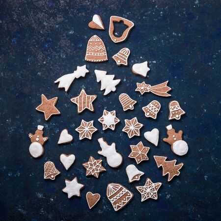 Homemade gingerbread cookie decorated with white icing on a blue background laid out in the shape of a Christmas tree toy. Top view, flat lay