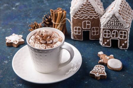 Cocoa with marshmallows in a white cup next to homemade gingerbread cookies and gingerbread houses. Christmas greeting card