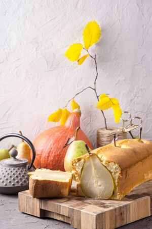 A pie with whole pear fruits as an autumn homemade product next to pumpkins, yellow leaves and a gray teapot Stock Photo