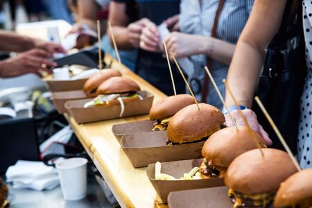 Street food many burgers with meat and cheese and french fries in craft packaging. The food line at the festival