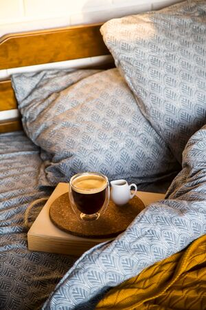 Coffee in a modern cup with a double bottom on a tray with creamer in bed with blue textured linen. Good morning concept