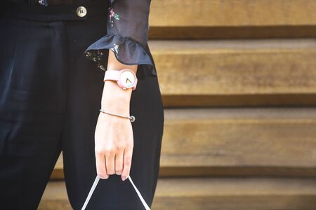 Fashionable young caucasian woman with a modern watch and a bracelet on her hand holding handbag on wooden background. Copy space. Stock Photo