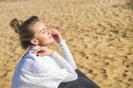A young beautiful Caucasian girl with a bun of hair on her head in a white boho jacket is sitting on the sand by the sea. Enjoying travel and nature concept.