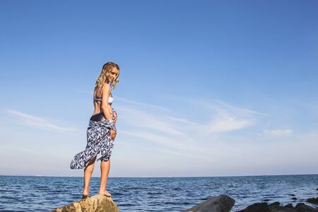 A beautiful slender Caucasian girl stands on the seashore turns around and looks down standing with her back to the camera. Standard-Bild - 134938469