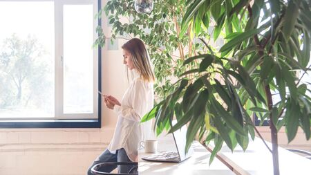 Modern business woman at coffee shop or coworking interior has breaks with smartphone in her hands. Freelancer remote work concept.