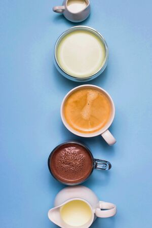 Classic blue background with different types of hot drinks - coffee, matcha, cocoa and white creamers with milk and cream.