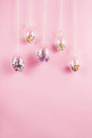 Easter eggs are transparent and filled with small colorful flowers hanging on a rope on a pink background. Minimalistic holiday decoration. Banque d'images