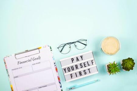 Bright modern notebooks and checklists for keeping personal finances and creating savings. Layout on a bright neo-mint background with copy space.