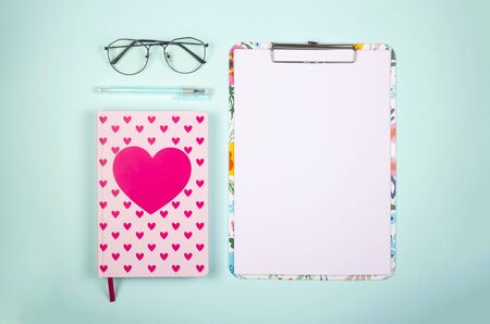 Blank paper on colored clipboard with copy space on a bright neo-mint background with glasses. Top view, flat lay.